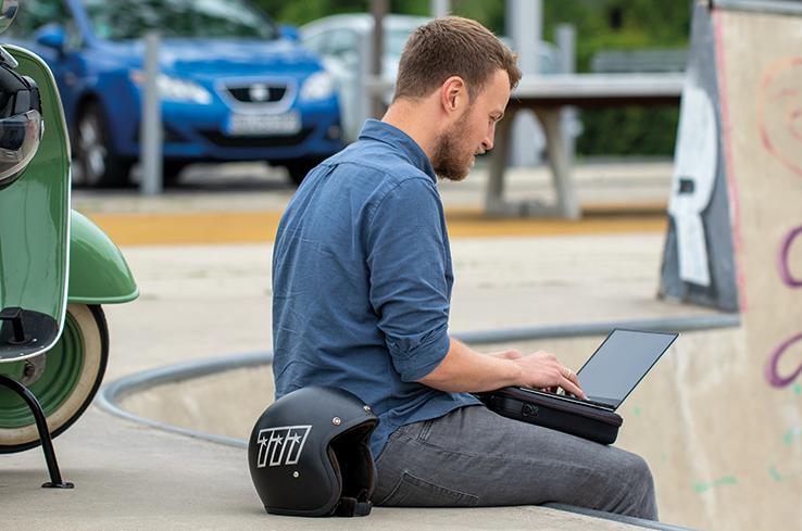 Junger Mann sitzt mit Laptop auf dem Schoß und nutzt die TROIKA Lapotoptasche als Unterlage.