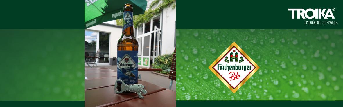 Der Keiler-Flaschenöffner ist angelehnt an eine Hachenburger Bieflasche auf einem Tisch. Daneben Hachenburger sowie TROIKA Logo auf grünem Hintergrund.
