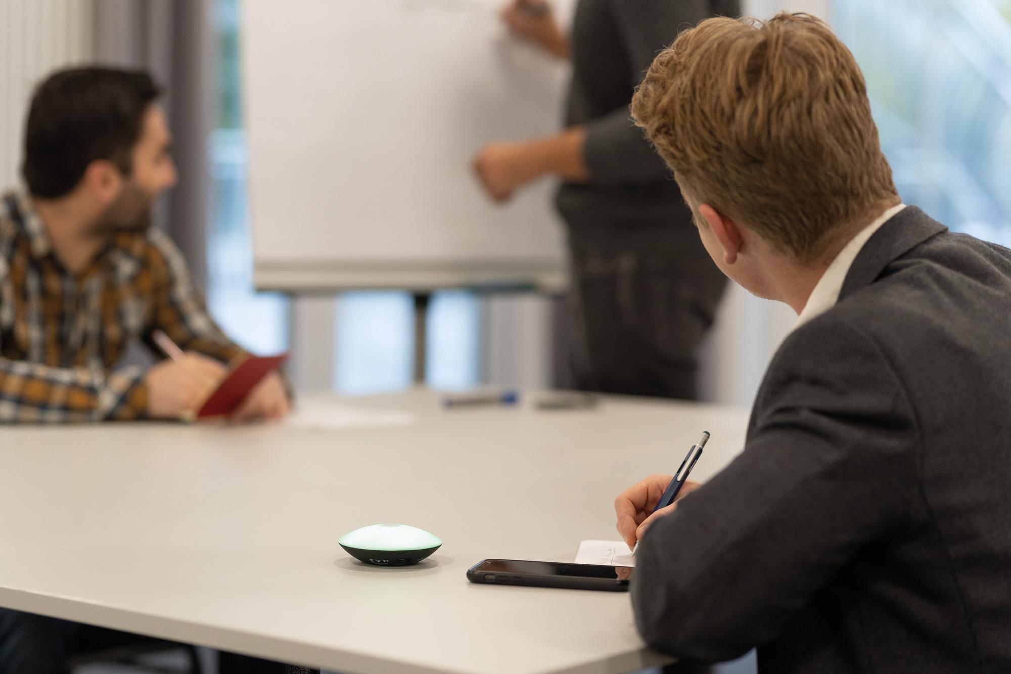 Junge Männer hören Präsentation zu und machen Notizen. Handy und TROIKA Meeting Timer liegen auf dem Tisch.
