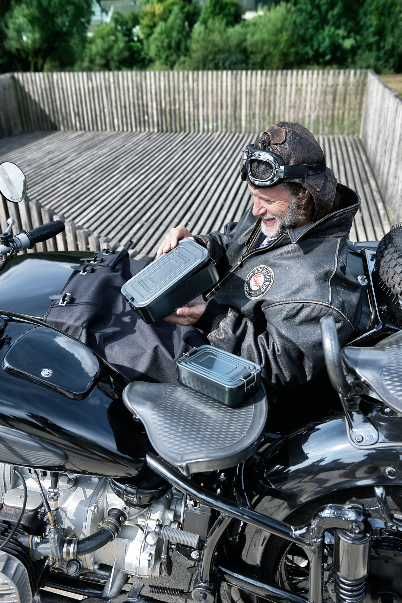 Man sits in old motorbike with a lunch box.