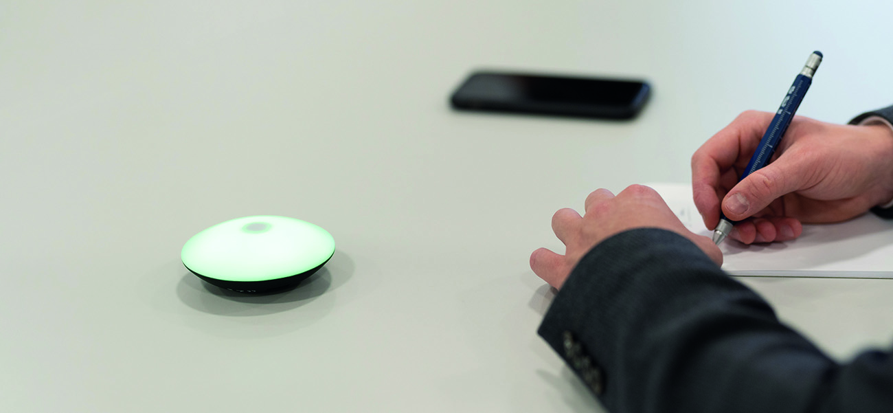 TROIKA Meeting Timer blinkt grün auf einem Schreibtisch neben zwei Männerhänden die etwas notieren. Daneben liegt ein Smartphone